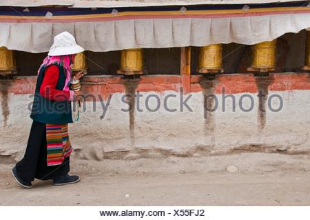Old woman turning prayer wheels, kingdom of Guge, Western Tibet, Tibet, Asia - Stock Photo