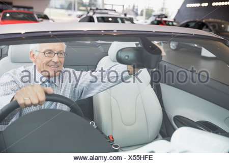Man adjusting rear-view mirror in showroom convertible - Stock Photo
