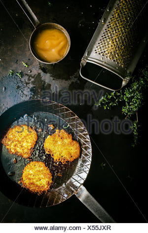 Delicious fresh fried potato fritters made from grated potato, fresh herbs and egg in a country kitchen with a vintage grater, view from overhead with ingredients - Stock Photo