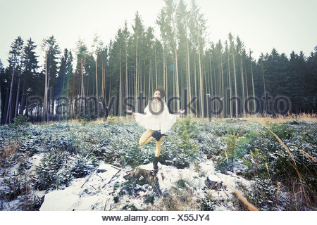 Mid adult woman practicing standing tree yoga pose in forest - Stock Photo