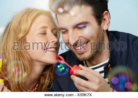 Germany, Dusseldorf, Young couple making soap bubbles - Stock Photo