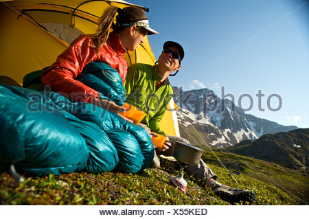 Hikers enjoy a morning meal at camp on the Williwaw Lakes Trail in Chugach State Park near Anchorage,Southcentral Alaska, Summer - Stock Photo