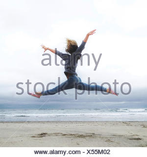 USA, Oregon, Tillamook County, Rockaway Beach, Young woman practicing ballet on beach - Stock Photo