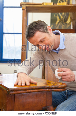 Carpenter buffing wooden table - Stock Photo