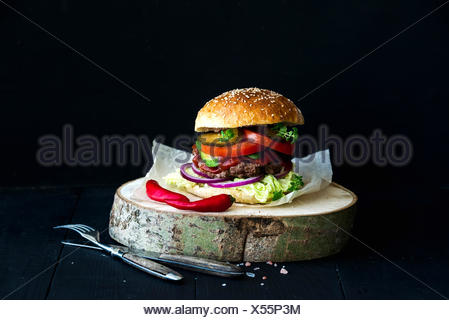 Fresh homemade burger on wooden serving board with red chili peppers over black  background - Stock Photo