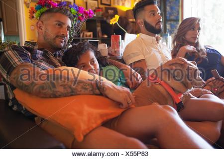 Girl and family on living room sofa watching TV - Stock Photo