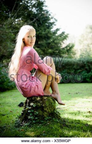 Woman sitting on stump outdoors - Stock Photo