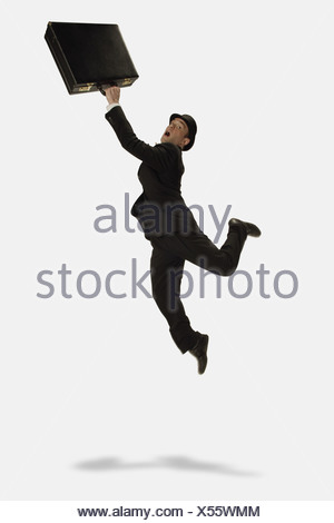Businessman jumps in air with briefcase - Stock Photo