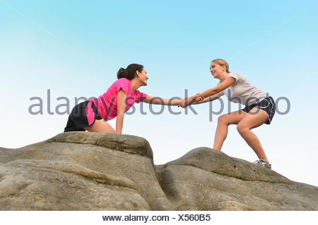 Young female runner helping friend to top of rock formation - Stock Photo