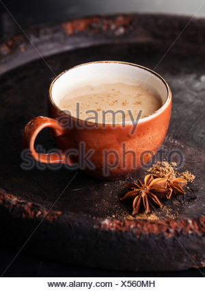 Indian masala tea with spices and milk on dark background - Stock Photo