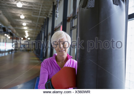 Portrait of smiling woman boxing at gym - Stock Photo