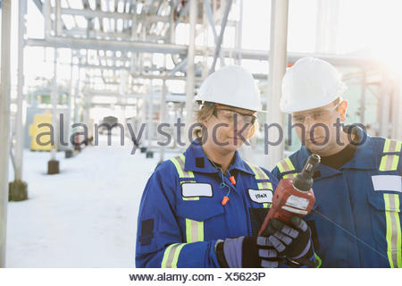 Workers using testing equipment at snowy gas plant - Stock Photo