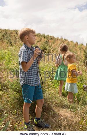 Three young children exploring, outdoors, boy using binoculars - Stock Photo