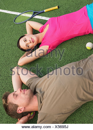 Young couple lying on tennis court - Stock Photo