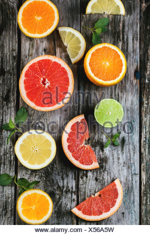 Set of sliced citrus fruits lemon, lime, orange, grapefruit with mint over wooden background. Top view. - Stock Photo