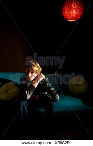 Bored teenage boy sitting on sofa indoors - Stock Photo