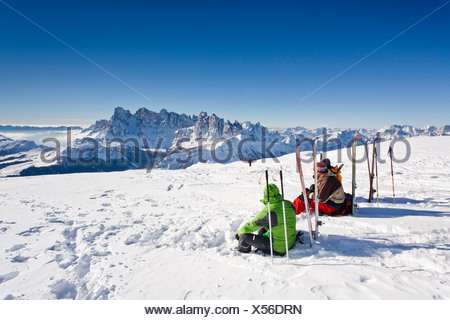 Ski tourers taking a break on the summit of Mt Uribrutto, above Passo Valles, Dolomites, Pale di San Martino mountains and the - Stock Photo