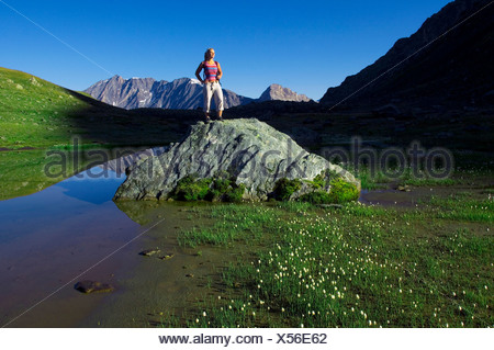 young woman standing on a rock at a mountain lake, France, Vanoise National Park - Stock Photo