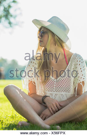 Young woman wearing white sunhat sitting cross legged - Stock Photo