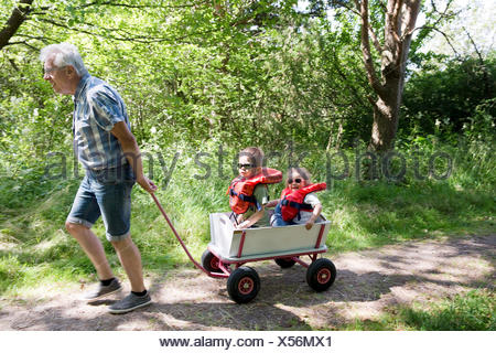 Grandfather pulling children in cart - Stock Photo