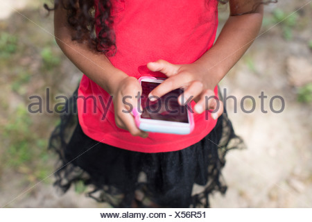 Young girl in park playing hand held video game - Stock Photo
