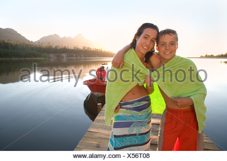 Teenage boy and girl 12 14 standing on lake jetty at sunset sharing green towel smiling portrait - Stock Photo