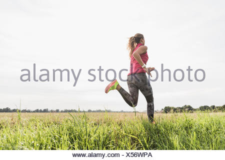 Young woman running in rural landscape - Stock Photo