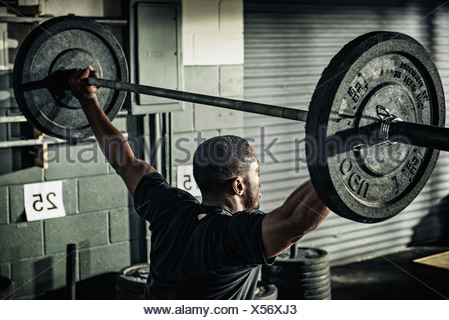Young man holding up barbell in gymnasium - Stock Photo
