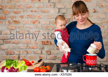 Mother carrying baby daughter whilst preparing lunch - Stock Photo