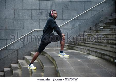 Young man exercising, stretching legs on steps, outdoors - Stock Photo