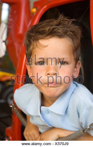 Portrait of a boy playing in a toy helicopter and making a funny face - Stock Photo
