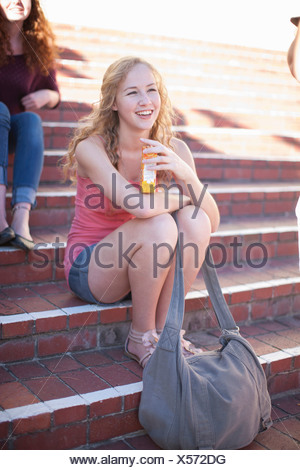 Young woman sitting on steps - Stock Photo