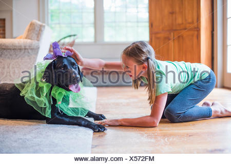 Young girl playing dress up with pet dog - Stock Photo