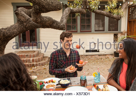 Friends sitting around table sharing barbecue food, man juggling fruit - Stock Photo
