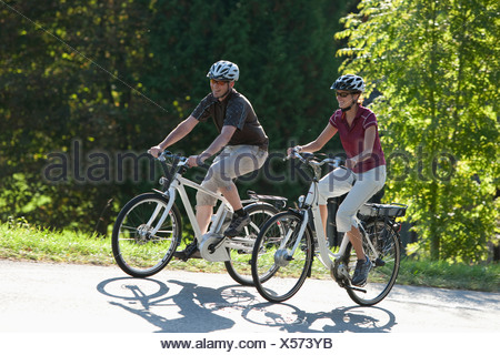 Germany, Bavaria, Man and woman riding electric bicycle - Stock Photo