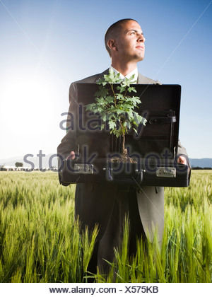 businessman holding a briefcase with a tree in it - Stock Photo