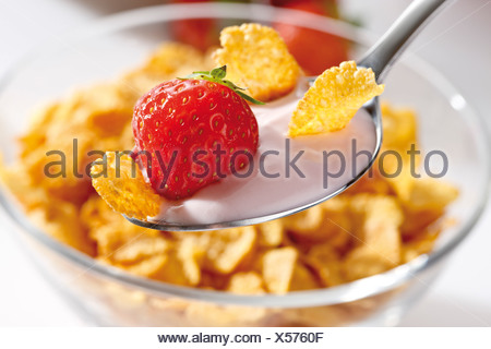 Strawberry yoghurt with cornflakes on a spoon - Stock Photo