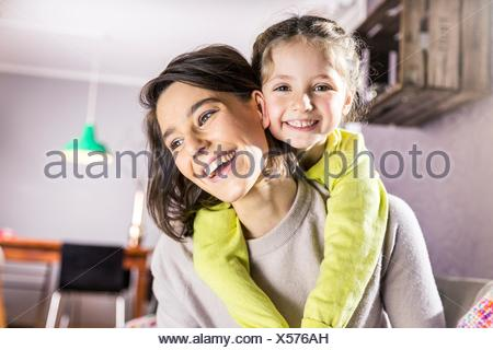Portrait of girl getting piggyback ride from mother in living room - Stock Photo