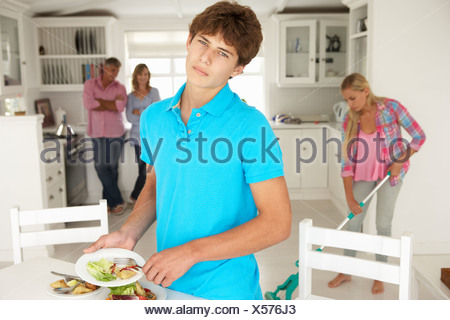 Teenagers reluctantly doing housework - Stock Photo