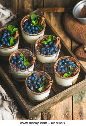 Homemade Tiramisu dessert in glasses with cinnamon, mint and fresh blueberry in wooden tray over rustic wooden background, top v - Stock Photo