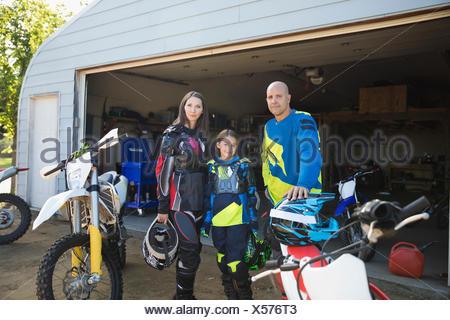 Portrait confident family near motorbikes in driveway - Stock Photo