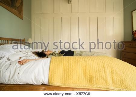 Side view of woman lying on bed with arms open