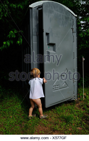 young boy opens door on portable toilet - Stock Photo