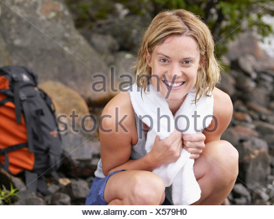 Woman crouching on rocks smiling with backpack in background. - Stock Photo