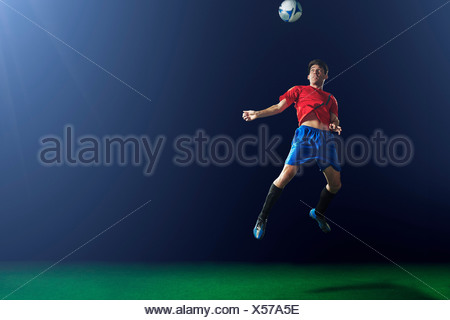 Young male soccer player heading ball - Stock Photo
