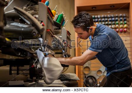 Worker preparing embroidery machine in t-shirt printing workshop - Stock Photo