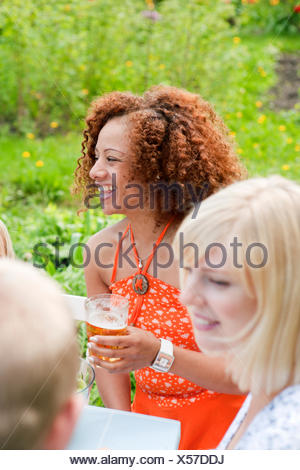 Woman with curly hair sitting at picnic table with glass of beer - Stock Photo