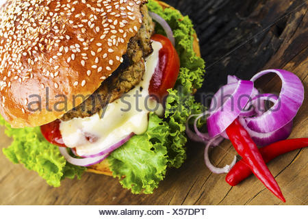 Yummy Hamburger with Veggies on Wooden Table - Stock Photo