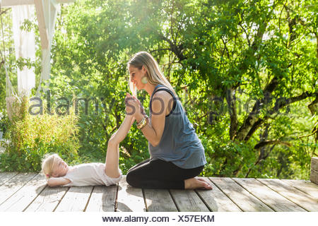 Mother and daughter practicing yoga on wooden terrace - Stock Photo