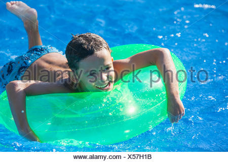 Boy lying on inflatable ring in garden swimming pool - Stock Photo